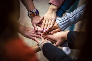 menschen die ihre händer aufeinander legen